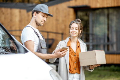 delivery man hold a phone parcel track while female receiving a parcel
